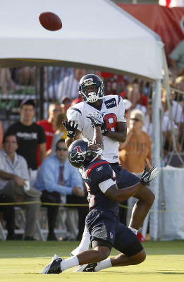 Texans receiver Lestar Jean jumps over cornerback Brandon Harris for a pass. Photo: Karen Warren, Chronicle