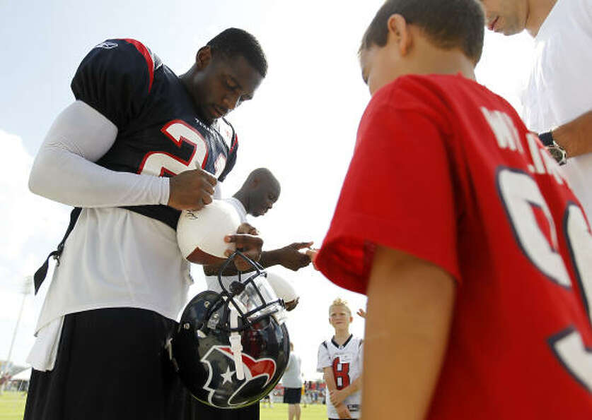 Texans cornerback Brice McCain signs an autograph for Julian Mares, 8, after the morning session.