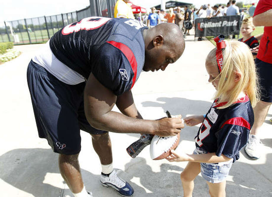 Texans linebacker DeMeco Ryans signs an autograph for Ashleigh Roder, 7 after the morning session. Photo: Karen Warren, Chronicle