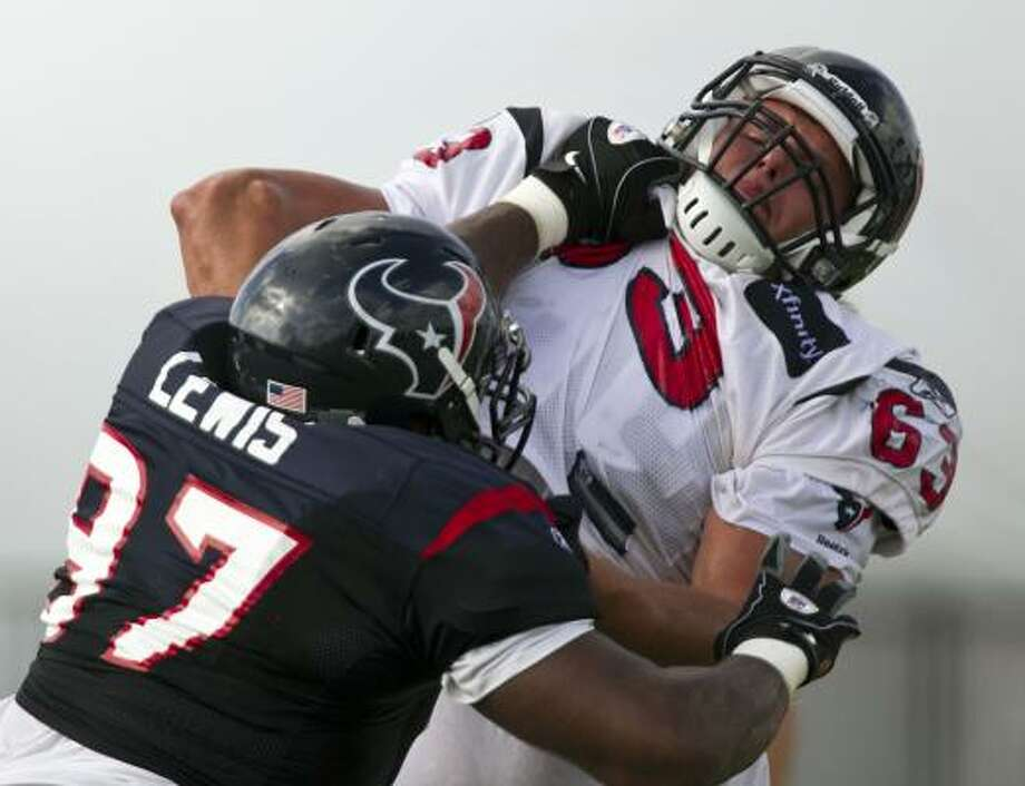 Texans linemen Damione Lewis, left, and Howard Barbieri shove each other during a blocking drill. Photo: James Nielsen, Chronicle