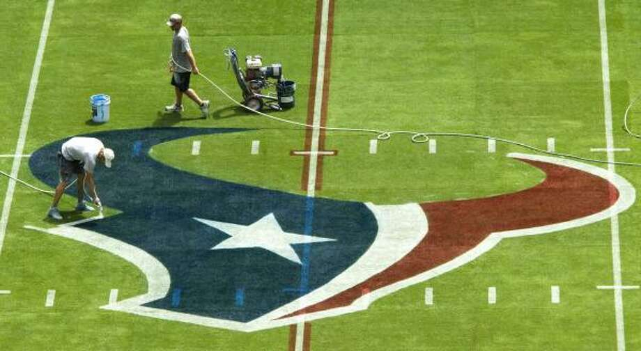 Derek Hutchinson, left, and Brandon Smith paint the Texans logo at the 50-yard line. The Texans open the preseason on Monday night against the Jets. Photo: Brett Coomer, Chronicle