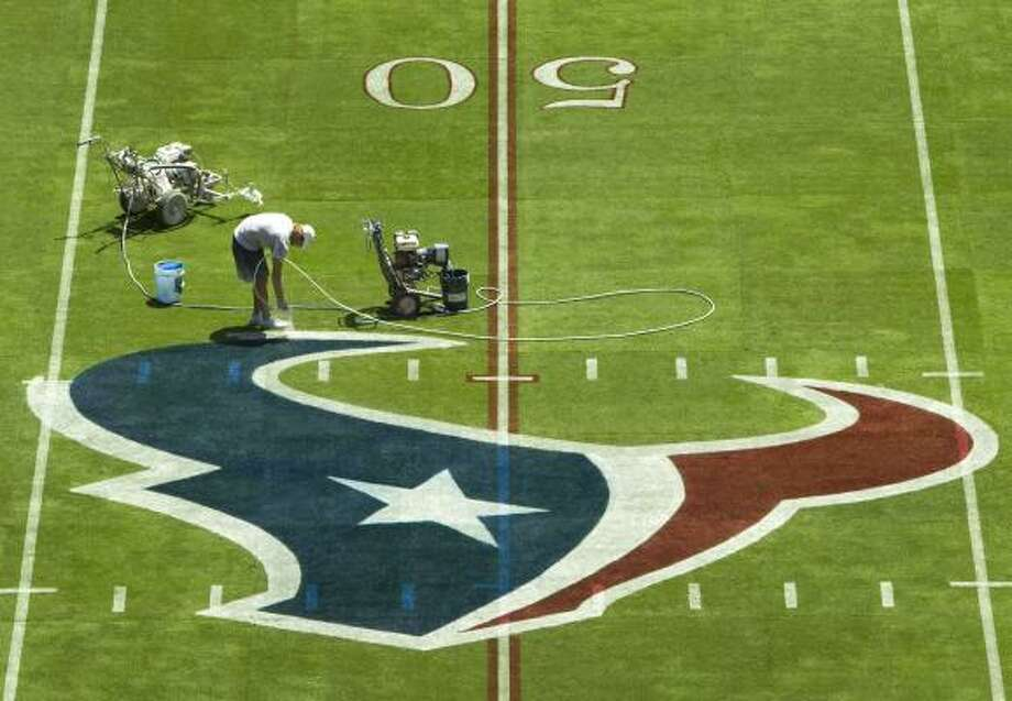 Derek Hutchinson paints the last edge of the Texans logo at the 50-yard line. Photo: Brett Coomer, Chronicle