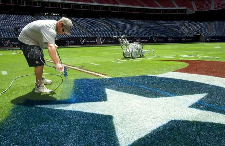 Brandon Smith paints the Texans logo at the 50-yard line of Reliant Stadium. The Texans open the preseason on Monday night against the Jets. Photo: Brett Coomer, Chronicle