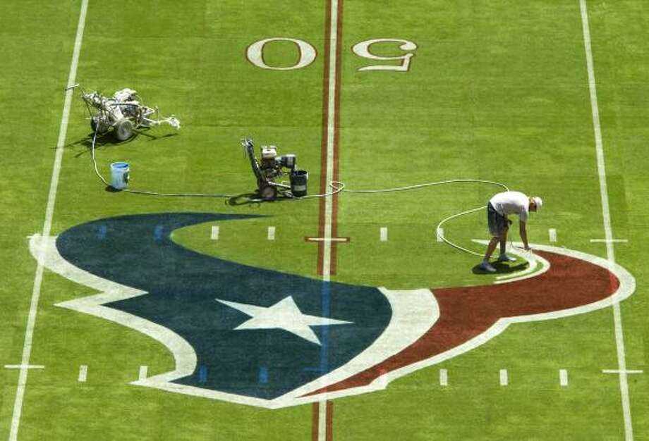 Derek Hutchinson touches up some of the red of the Texans logo at the 50-yard line. Photo: Brett Coomer, Chronicle
