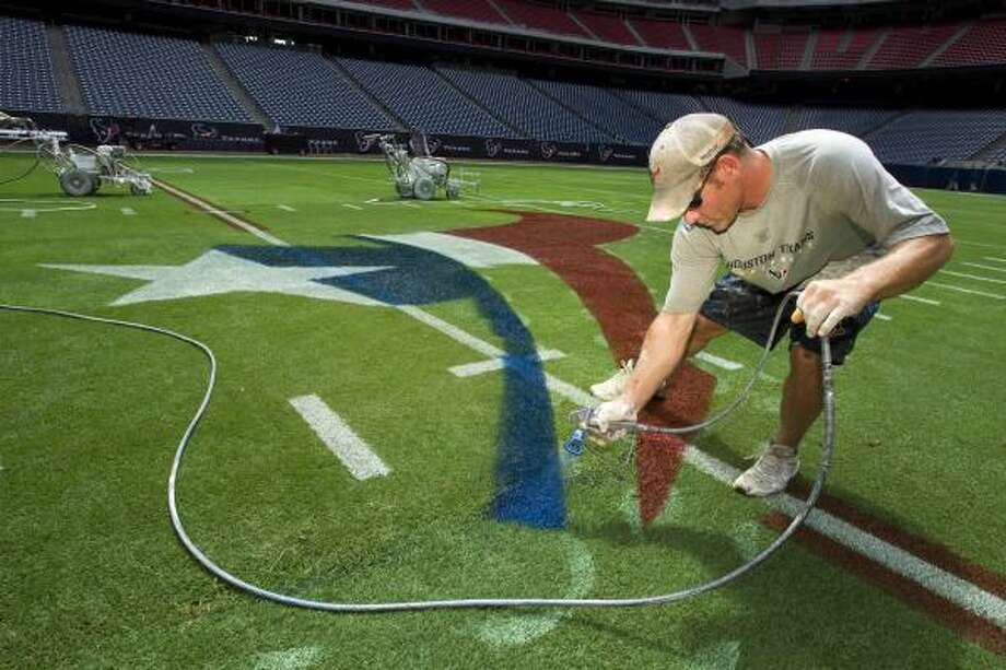 Brandon Smith paints the bottom of the Texans logo at the 50-yard line. Photo: Brett Coomer, Chronicle