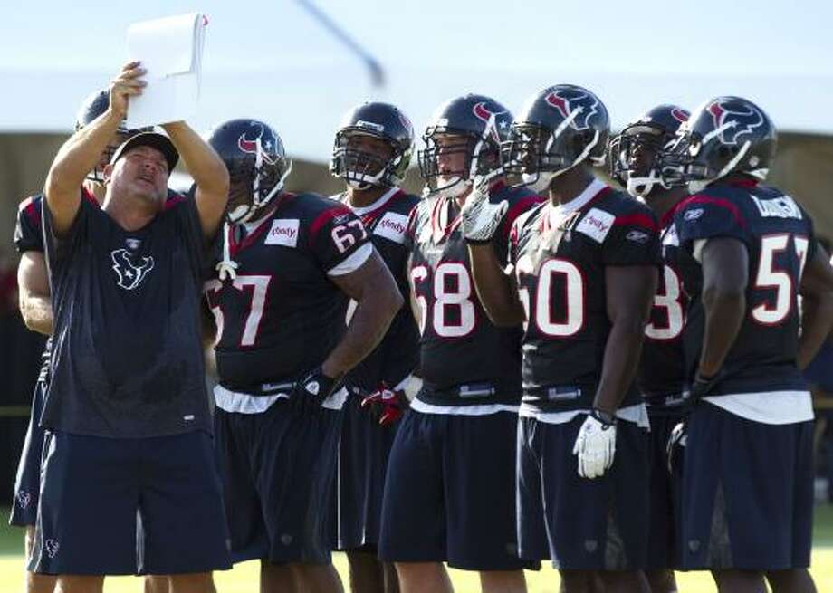 Houston Texans linebackers coach Reggie Herring, left, shows the defense a play during Texans training camp. Photo: Brett Coomer, Houston Chronicle