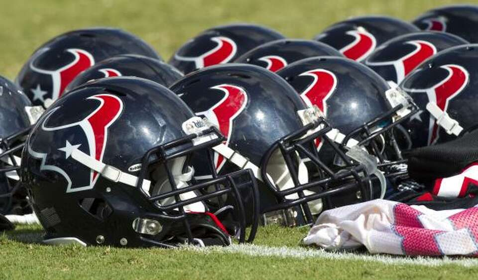 Houston Texans helmets lie on the field at the end of practice.