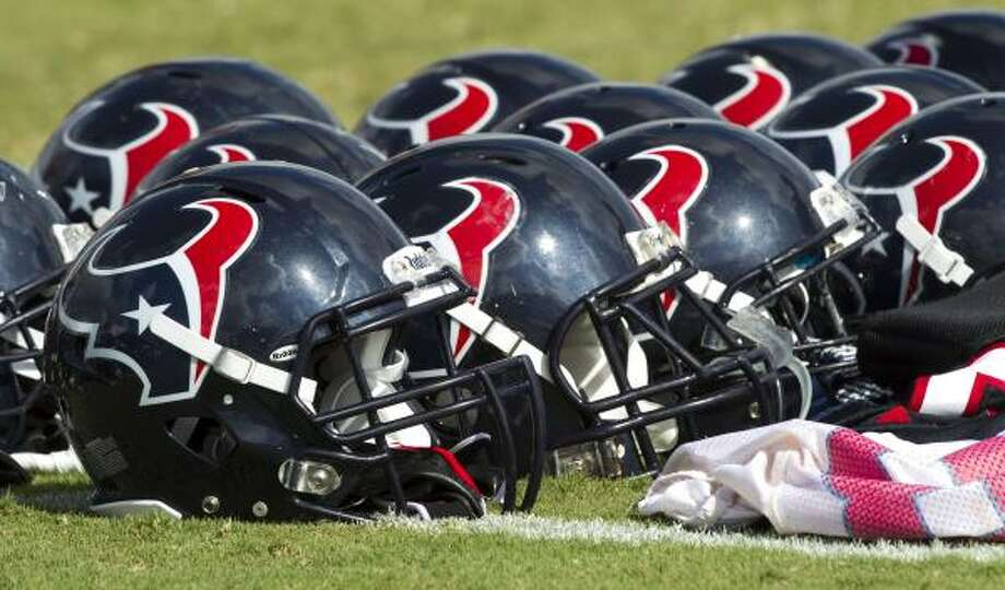 Houston Texans helmets lie on the field at the end of practice. Photo: Brett Coomer, Houston Chronicle