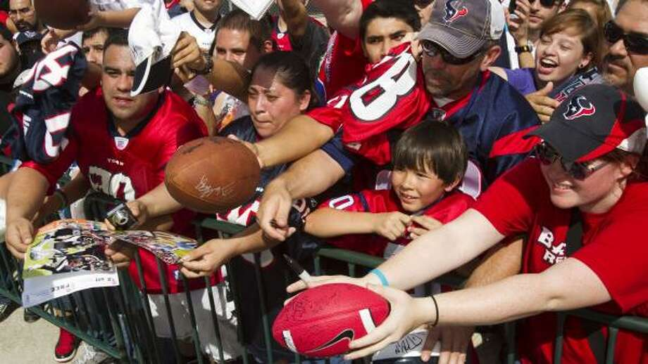 Houston Texans fans reach out for autographs during Texans training cam. Photo: Brett Coomer, Houston Chronicle
