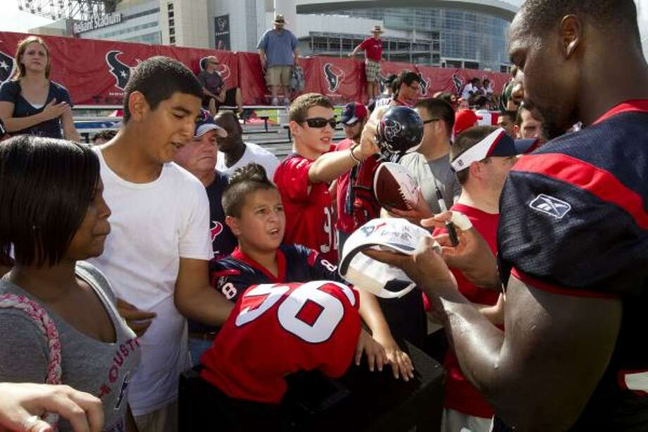 Houston Texans defensive end Antonio Smith, right, signs autographs during Texans training camp. Photo: Brett Coomer, Houston Chronicle