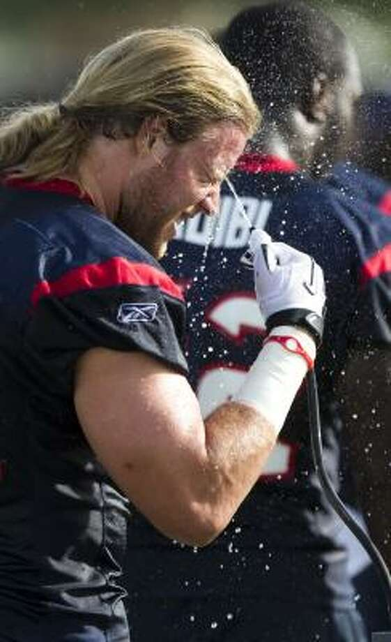 Texans linebacker Brooks Reed splashes his face with water. Photo: Brett Coomer, Chronicle