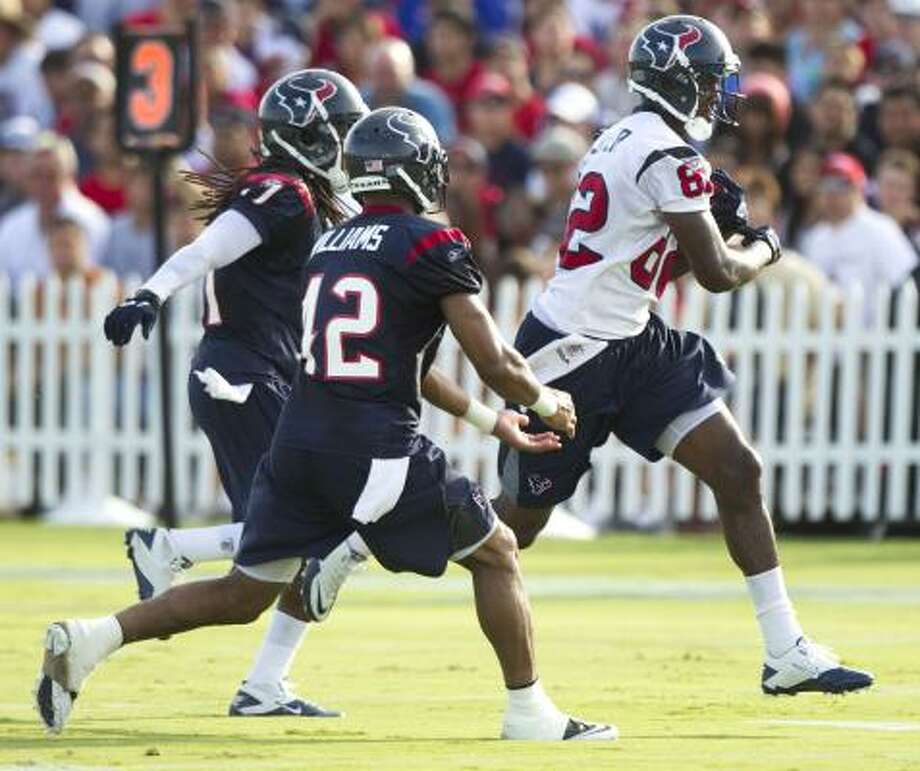 Texans wide receiver Terrence Toliver runs past safety Maurice Rolle (41) and safety Torri Williams (42). Photo: Brett Coomer, Chronicle