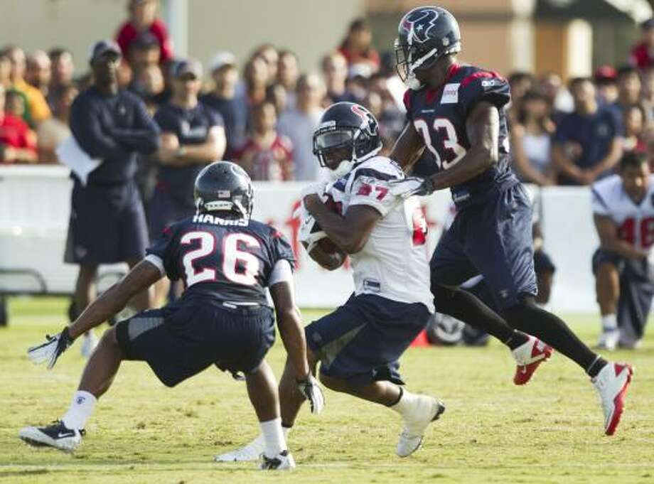 Texans running back Chris Ogbonnaya runs the ball between cornerback Brandon Harris (26) and safety Troy Nolan (33). Photo: Brett Coomer, Chronicle
