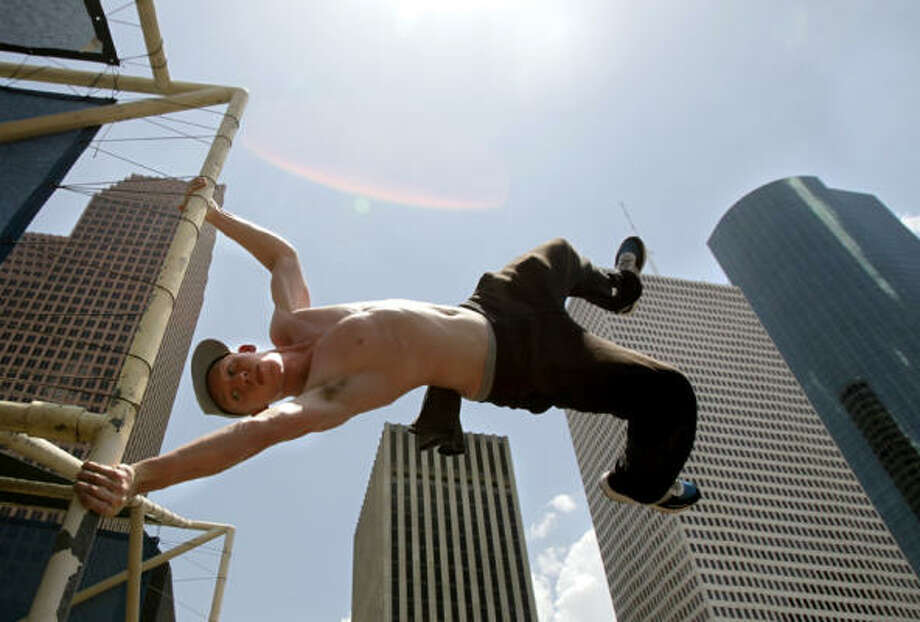 Peter Chasteen from the group Urban Movement, Inc., performs a parkour movement called a flagpole as he hangs from the covered area of Tranquility Park Saturday, July 2, 2011, in Houston. The sport, originating from France, combines the idea of scaling obstacles by running, climbing, and jumping. Photo: Cody Duty, Houston Chronicle