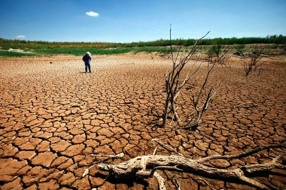 "Coke County Extension Agent, Garrett Gilliam, walks through a sun-scorched cracked lake bed where Lake E.V. Spence was once 30 feet deep. ""The morale is to survive,"" Gilliam said.  ""The good times will come again and we just keep praying to the good Lord that he'll bless us."" Photo: Michael Paulsen, Houston Chronicle"