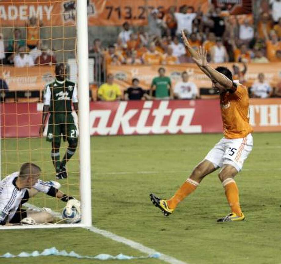 Forward Brian Ching #25 of the Houston Dynamo throws his arms up as he thought he scored on goalkeeper Troy Perkins. Photo: Bob Levey, Getty
