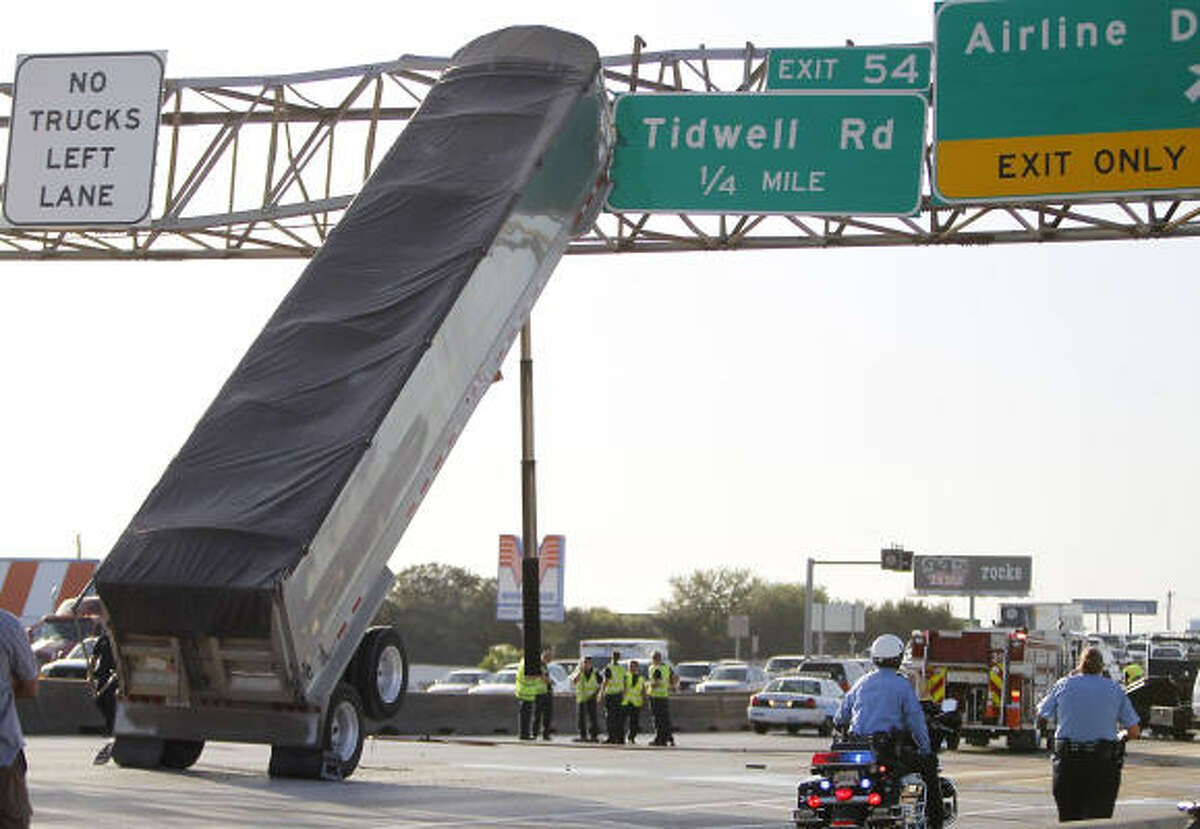 A trailer sits propped up on an interstate sign board after an accident on I-45 northbound near Airline Road.