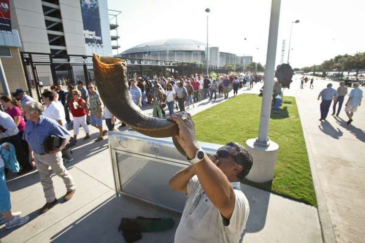 Jack Gonzales sounds a shofar, a horn used for religious purposes, outside Reliant Stadium as people arrive for The Response: A Call to Prayer for a Nation in Crisis rally Saturday in Houston.