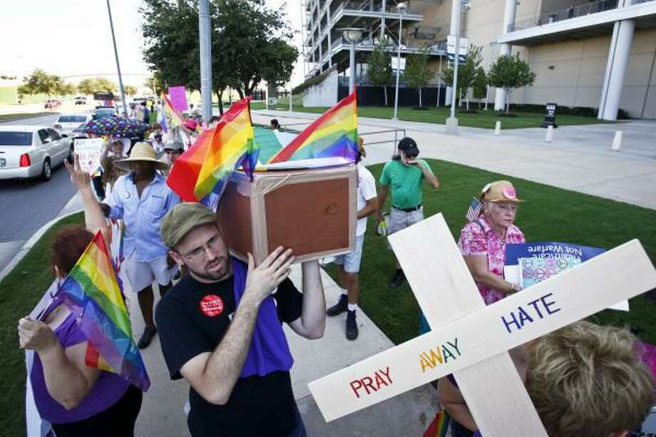 Jay Morris, left, carries a cardboard coffin to voice his protest. Photo: Michael Paulsen, Houston Chronicle