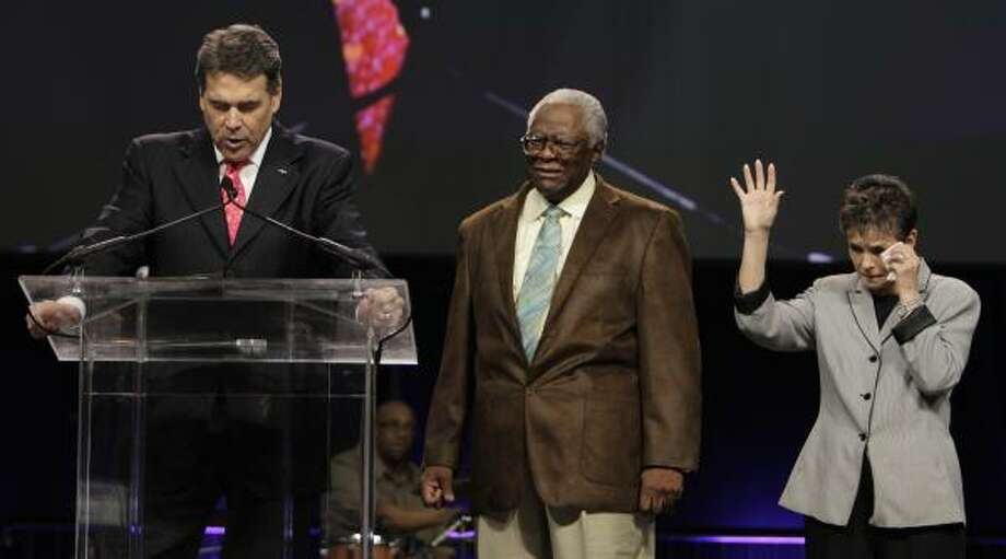 Perry prays on stage with the Rev. C.L. Jackson and Alice Patterson. Photo: Melissa Phillip, Houston Chronicle