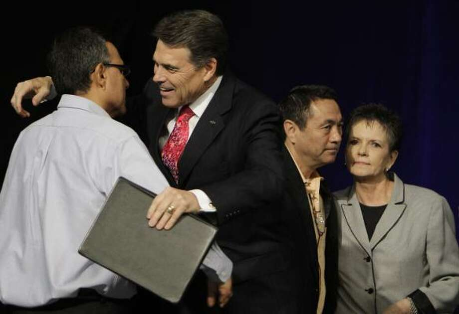 Luis Cataldo, left, director of The Resonse, hugs Perry with Doug Stringer, Rapid Fire prayer captain, and Alice Patterson, right, after the governor read Scripture and gave a prayer. Photo: Melissa Phillip, Houston Chronicle
