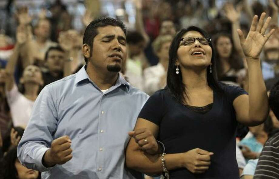 Ismael Gomez, left, and Lidia Gomez, of Houston, join in a prayer. Photo: Melissa Phillip, Houston Chronicle