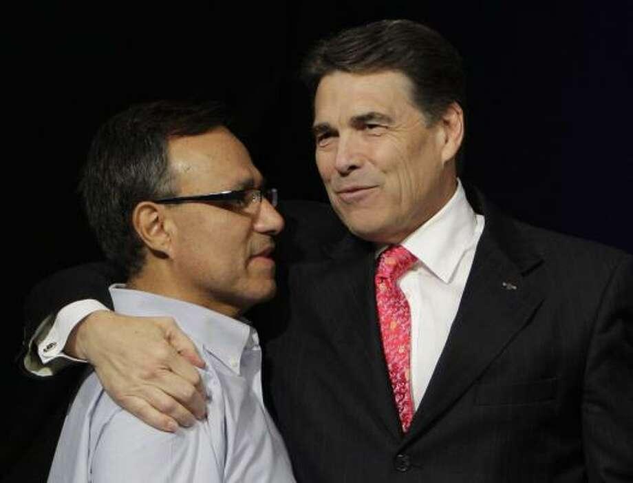 Perry hugs Luis Cataldo, director of The Resonse. Photo: Melissa Phillip, Houston Chronicle