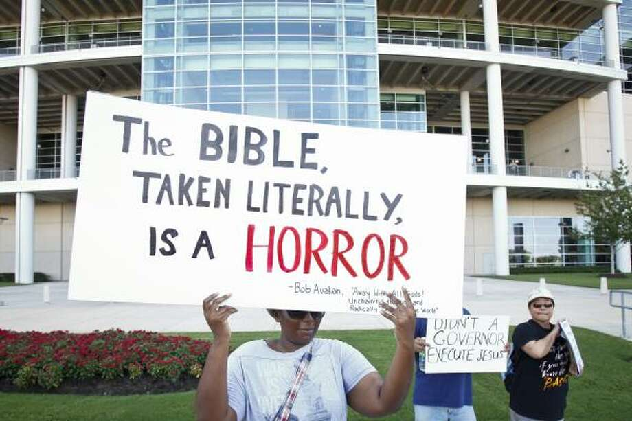 A woman who asked not to be identified holds a protest sign outside Reliant Stadium. Photo: Michael Paulsen, Houston Chronicle