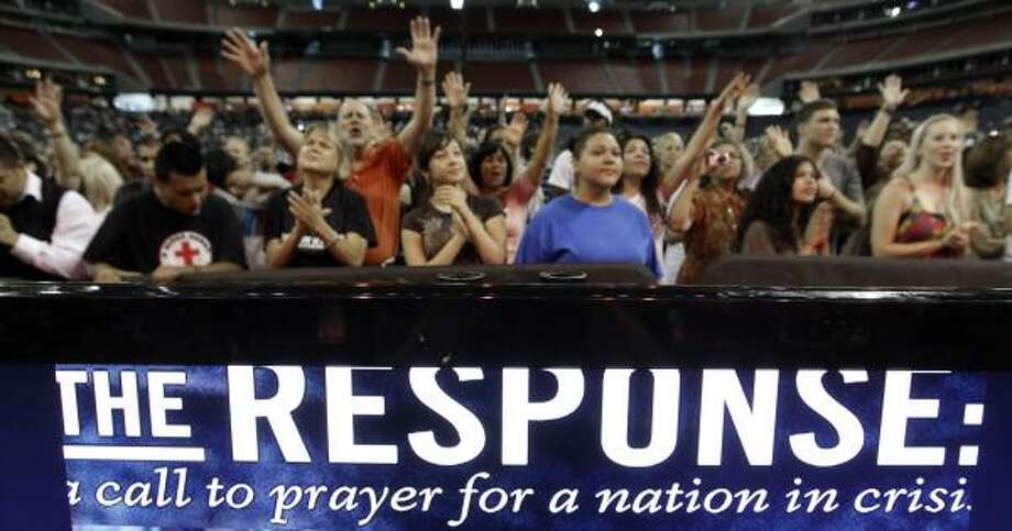 Participants sing and pray in Reliant Stadium. Photo: David J. Phillip, Associated Press