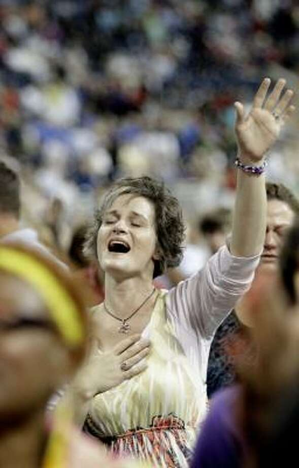 A woman prays at The Response. Photo: David J. Phillip, Associated Press