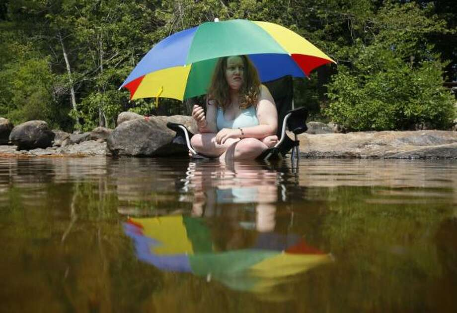 Hailey Crowell, 14, of Scarborough, Maine, tries to stay while sitting in the Saco River under an umbrella as temperatures climb into the upper 90s in Limington, Maine. Photo: Robert F. Bukaty, Associated Press