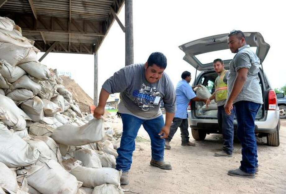Cameron County employee Luis Gallegos grabs a sandbag from a pile as cars arrive to receive them prior to Tropical Storm Don's predicted landfall, at The Cameron County Warehouse Precinct 1 on Friday, July 29, 2011 in Brownsville. Photo: Paul Chouy, Associated Press