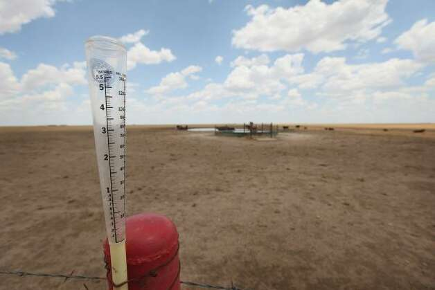 An empty rain guage is strapped to a fence post on the edge of a pasture near Canadian, Texas. A severe drought in the region has caused shortages of grass, hay and water, forcing ranchers to thin their herds or risk losing their cattle to the drought. The past nine months have been the driest in Texas since record keeping began in 1895, with 75% of the state classified as exceptional drought, the worst level. Photo: Scott Olson, Getty