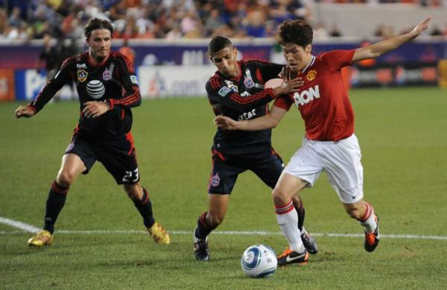 MLS All-Star Geoff Cameron, center,fights for the ball with Manchester United's Ji-Sung Park as All-Star David Beckham looks on. Photo: DON EMMERT, Getty