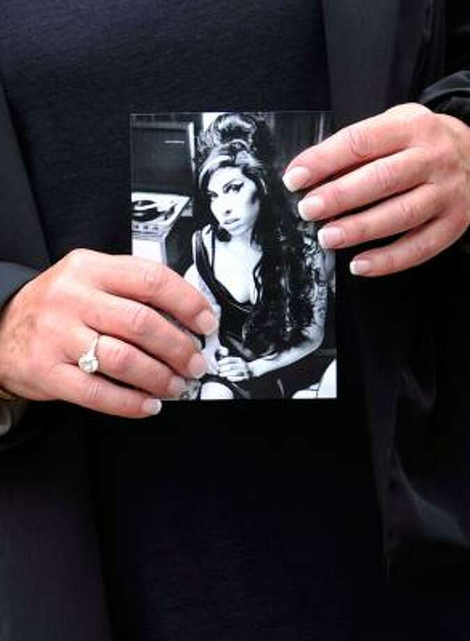 A mourner holds a photograph of Amy Winehouse on the way to the funeral service. Photo: Gareth Cattermole, Getty