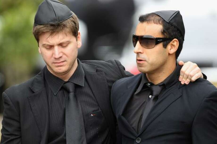 Two men react after the funeral service of singer Amy Winehouse at Edgwarebury Lane cemetery. Photo: Dan Kitwood, Getty