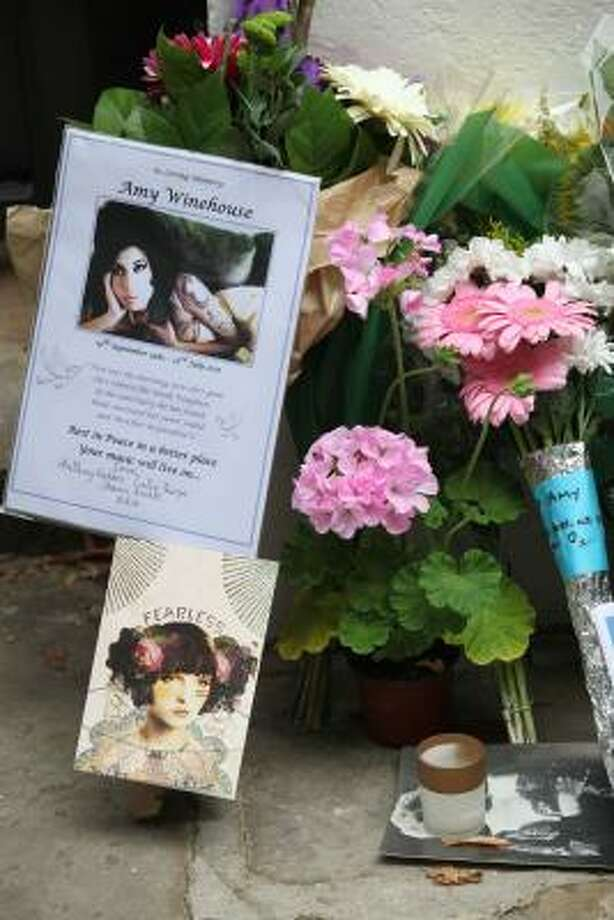 General view of flowers, candles and cards at Amy Winehouse's home in Camden Square. Photo: Neil Mockford, Getty