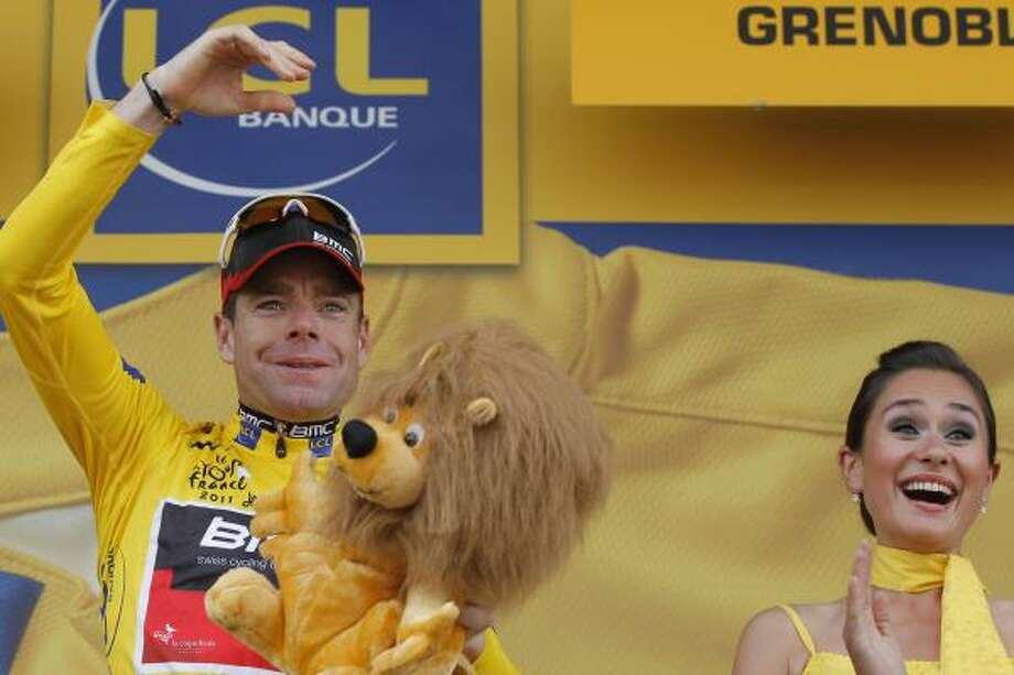 July 23    20th Stage  New overall leader Cadel Evans of Australia throws flowers to cheering spectators on the podium of the 20th stage of the Tour de France. Photo: Christophe Ena, Associated Press