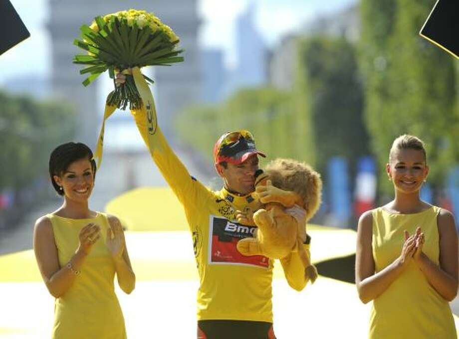 July 24   Final Stage  Tour de France winner Cadel Evans of Australia, wearing the overall leader's yellow jersey, kisses the trophy on the podium in Paris, France. Photo: Bernard Papon, Associated Press
