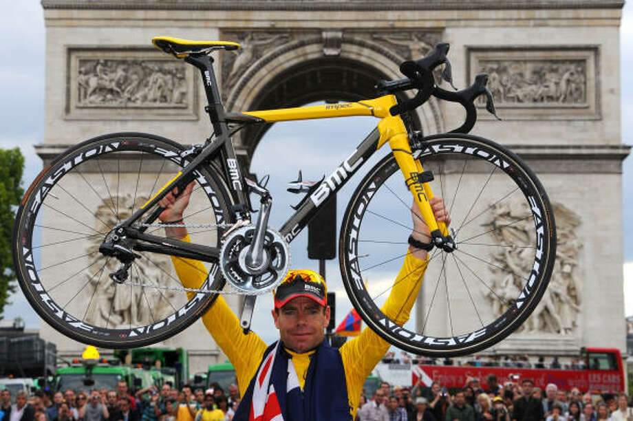 Australia's Cadel Evans lifts his bicycle in front of the Arc de Triomphe during the parade on the famous Champs-Elysees avenue in Paris, after he won the 2011 Tour de France. Photo: PASCAL PAVANI, Getty