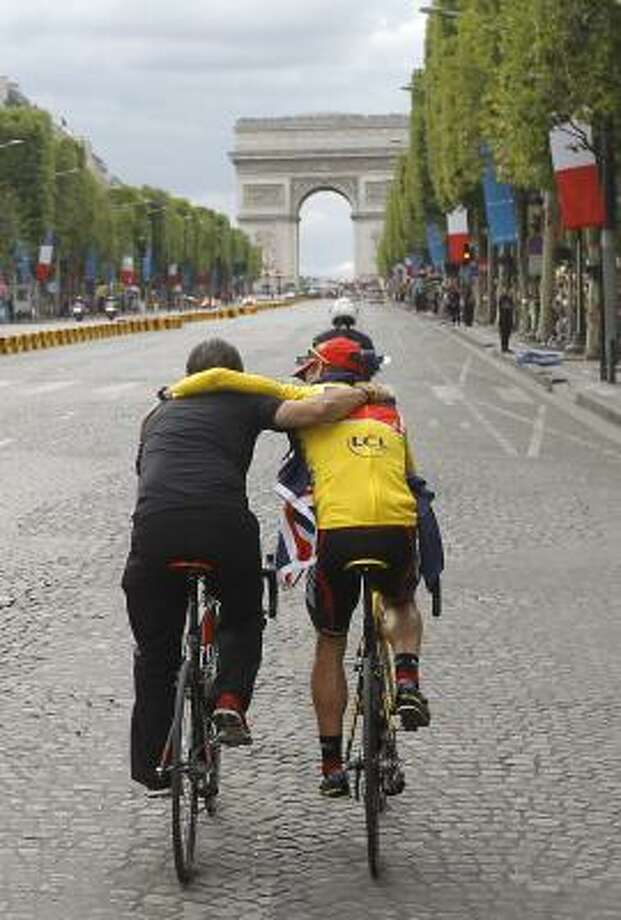 Tour de France winner Cadel Evans of Australia, wearing the overall leader's yellow jersey, cycles with his BMC teammates along the Champs Elysees during the victory parade after winning the Tour de France. Photo: Laurent Cipriani, Associated Press