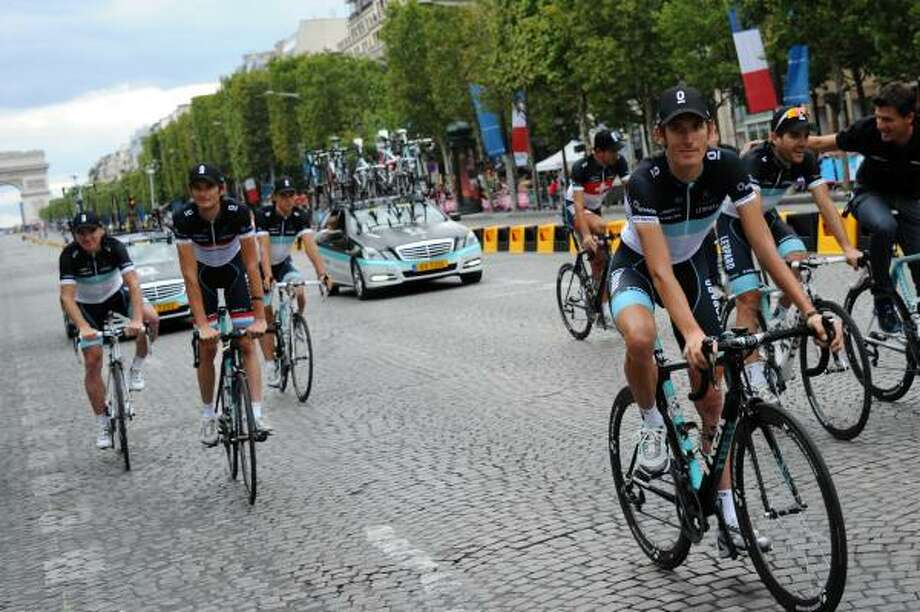 Second-placed in the overall standings, Luxembourg's Andy Schleck (R) and brother, third-placed in the overall standings, Luxembourg's national road champion Frank Schleck (C) ride during the parade on the famous Champs-Elysees avenue in Paris. Photo: MIGUEL MEDINA, Getty