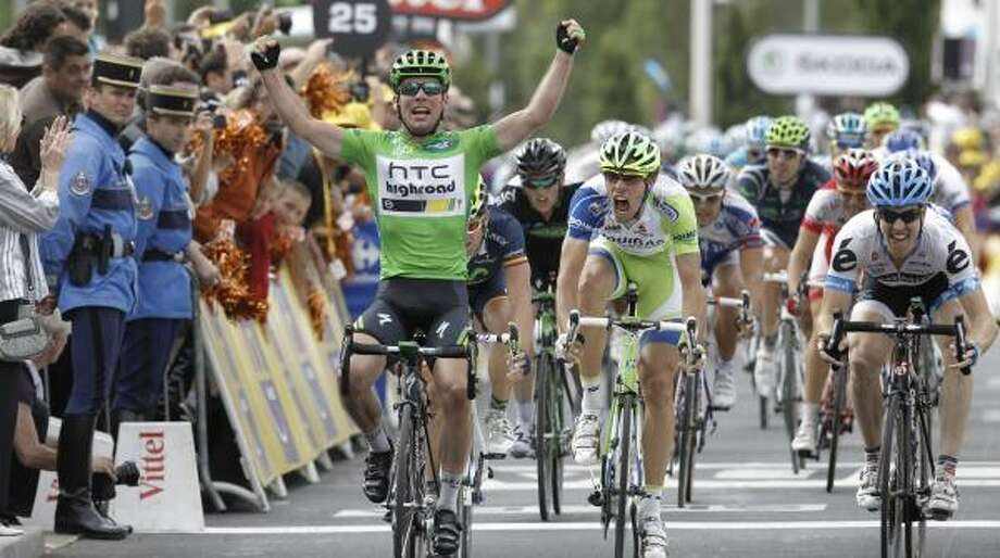 Mark Cavendish of Britain, left, crosses the finish line ahead of Tyler Farrar of the US, far right, and Daniel Oss of Italy, center. Photo: Laurent Cipriani, Associated Press