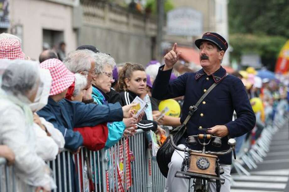 A man dressed as a old style French postman entertains the crowd during the 15th stage of the Tour de France. Photo: Michael Steele, Getty