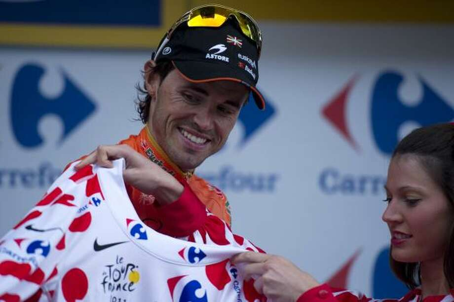 New Polka dot jersey of best climber and stage winner, Spain's Samuel Sanchez, celebrates on the podium after winning the 211 km and twelfth stage of the 2011 Tour de France cycling race run between Cugnaux and the 2.500 metres ski resort of Luz-Ardiden. Photo: LIONEL BONAVENTURE, Getty
