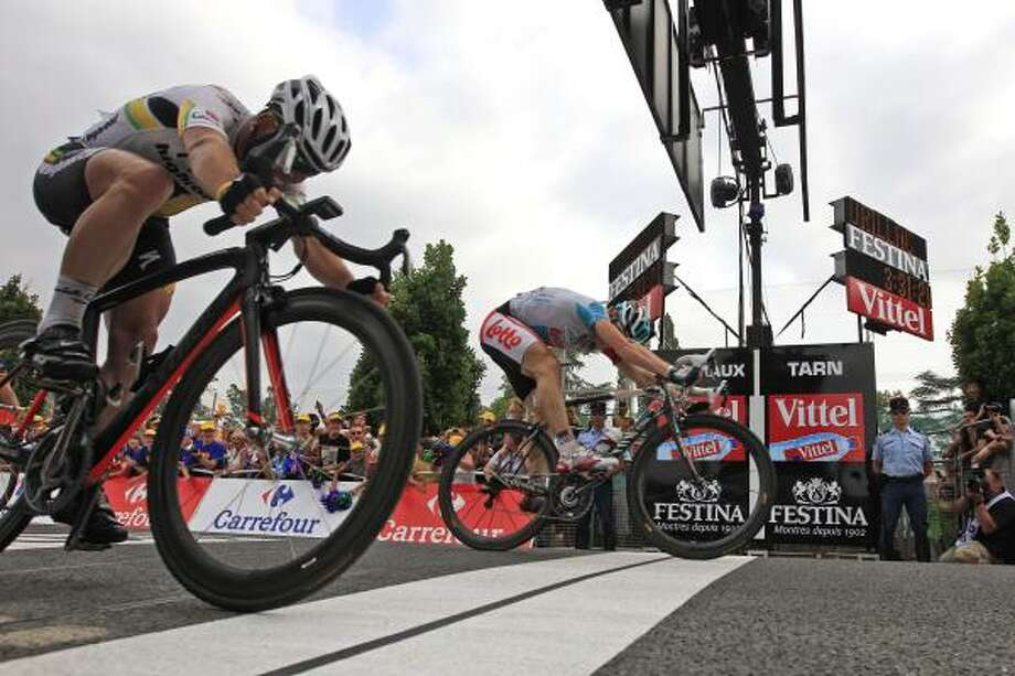 Andre Greipel of Germany, rear, pushes his wheel over the finish line ahead of second place Mark Cavendish of Britain, left, to win the 10th stage of the Tour de France. Photo: Peter Dejong, Associated Press