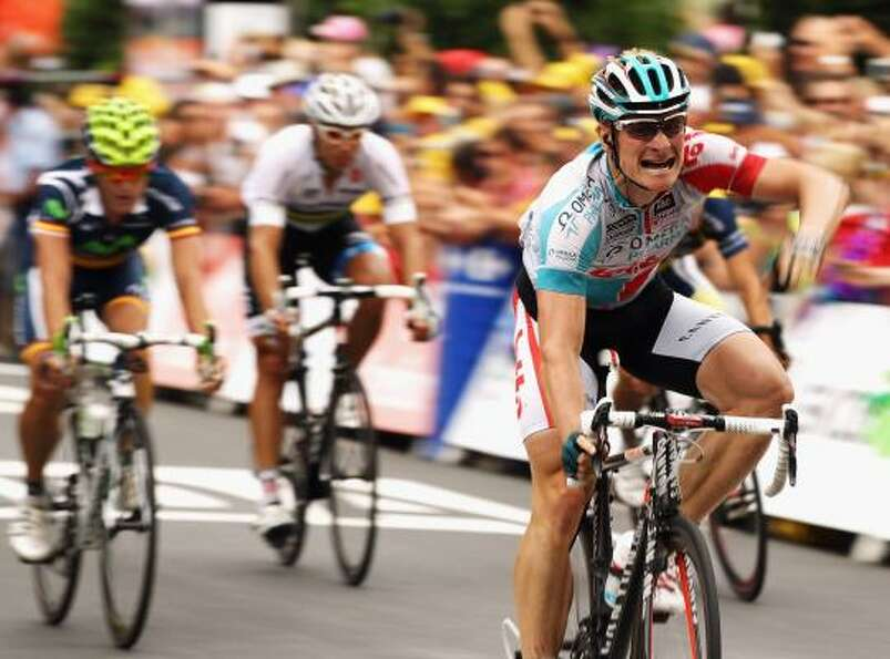 Andre Greipel of Germany and Omega Pharma-Lotto raises his arm in celebration as he crosses the line