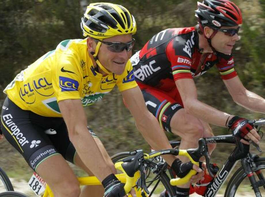 Thomas Voeckler of France, wearing the overall leader's yellow jersey, and Cadel Evans of Australia ride in the pack during the 10th stage of the Tour de France. Photo: Christophe Ena, Associated Press