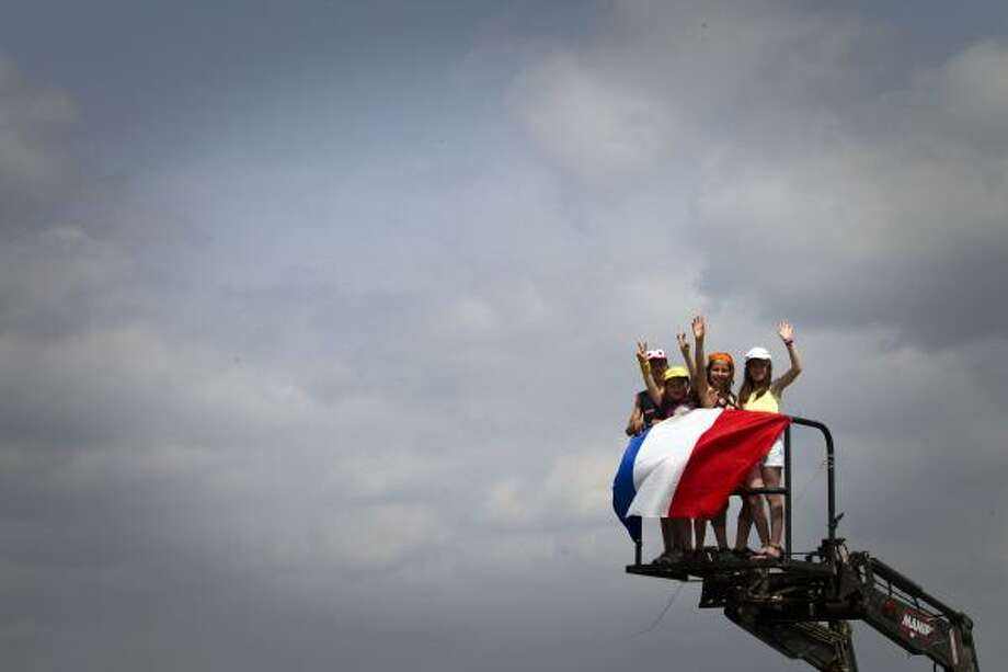 Young fans wave from a crane behind a French flag as they wait for riders during the 158 km and tenth stage of the 2011 Tour de France. Photo: JOEL SAGET, Getty