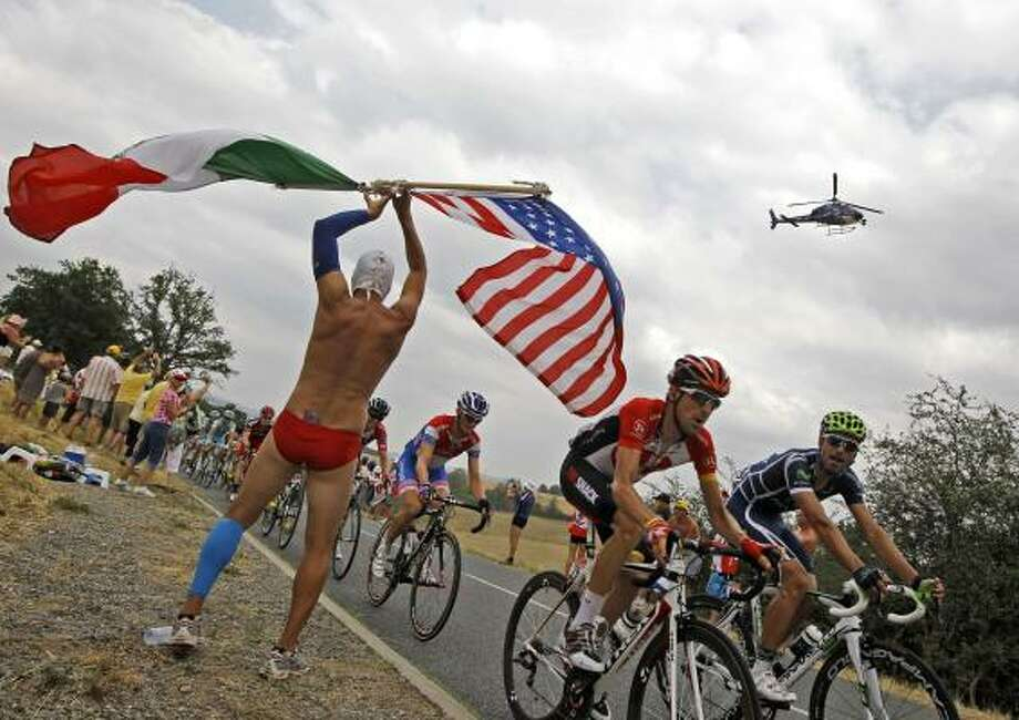 A cycling fan dressed as a wrestler waves the US and Mexican flag as the pack with Haimar Zubeldia of Spain, in red Radioshack shirt, passes during the 10th stage. Photo: Laurent Cipriani, Associated Press